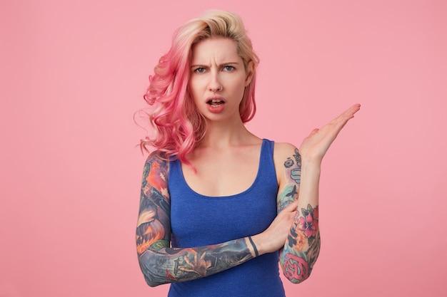 Giovane bella donna dai capelli rosa oltraggiata in maglietta blu, cipiglio e sguardo indignato, bocca spalancata in espressione di incomprensione. stand.