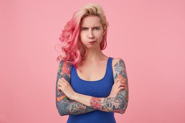 Молодая красивая возмущенная розоволосая женщина со скрещенными руками, возмущенными взглядами, непониманием выражения. стенды.
