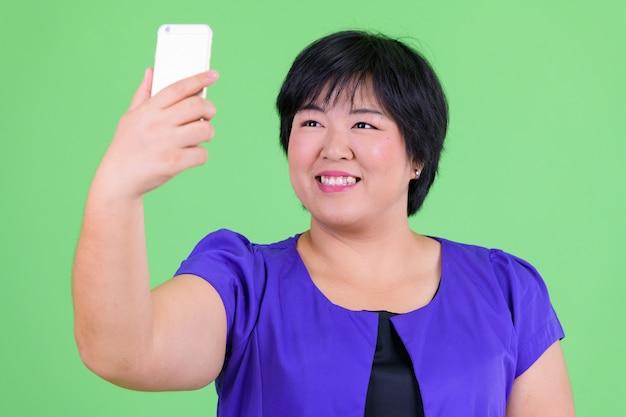 녹색 벽과 크로마 키에 대해 젊은 아름다운 과체중 아시아 여자