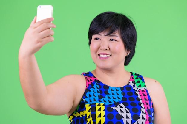 녹색 벽 크로마 키에 대해 파티를 준비 젊은 아름다운 과체중 아시아 여자