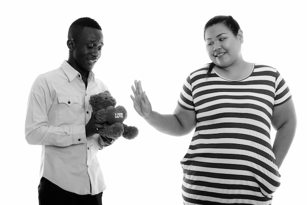 Young beautiful overweight asian woman and young african man together as couple in black and white