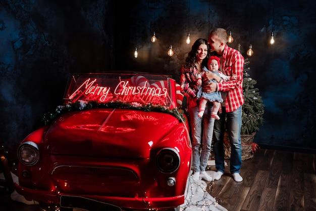 スタジオでレトロな車の近くで楽しんでいる彼らの小さなかわいい娘を腕に抱いて若い美しい親。クリスマスの家族の外観。