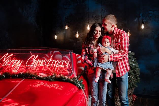 Молодые красивые родители, держащие свою маленькую милую дочь на руках, веселятся возле ретро-автомобиля с текстом рождества