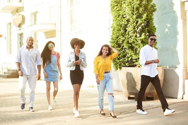 さまざまな国籍の若い美しい人々が街を歩き回り、話します
