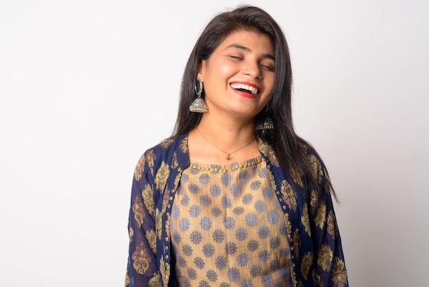 Молодая красивая персидская женщина в традиционной одежде у белой стены