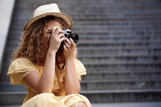 Giovane bello fotografo che cammina intorno alla città.