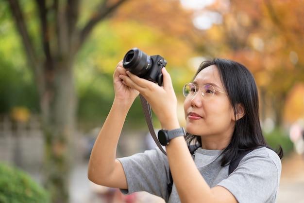 Молодой красивый фотограф с профессиональной камерой, принимая фото красивые Premium Фотографии