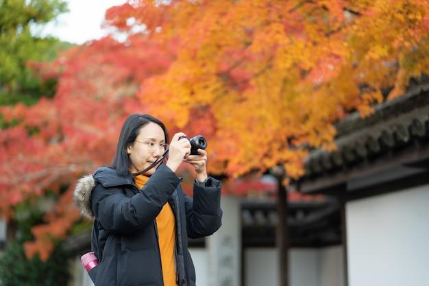 Молодой красивый фотограф с профессиональной камерой фотографировать