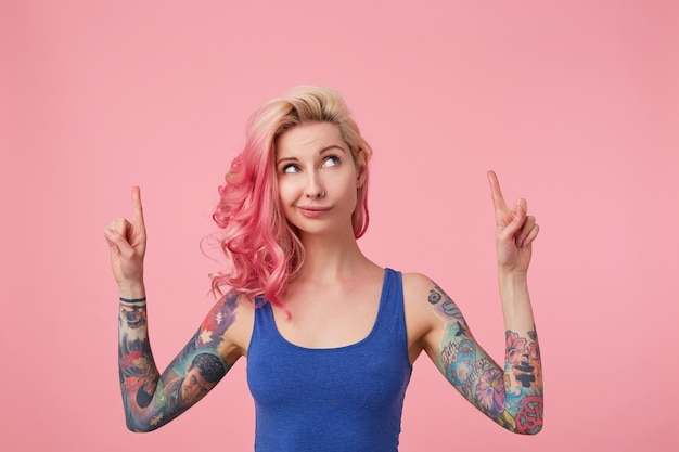 Young beautiful pink haired lady in blue t-shirt with arms raised, doubts something, looks up and wants to draw your attention pointing with fingers on the copy space, standing.