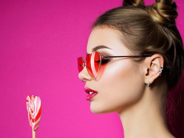 若い美しい遊び心のある女性は、ハート型のロリポップを保持しています。バレンタインデー、愛やテーマパーティーのコンセプト。スモーキーな目とピンクの唇のメイク。