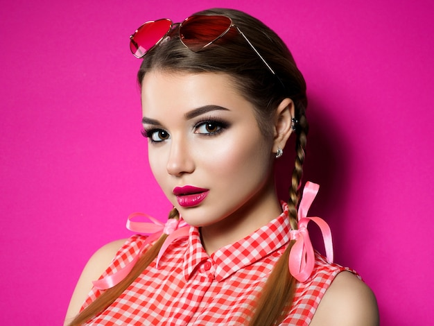 若い美しい遊び心のある女性は、彼女のハート型の赤い眼鏡を見ています。バレンタインデー、愛やピンナップのテーマパーティーのコンセプト。スモーキーな目と赤い唇のメイク。