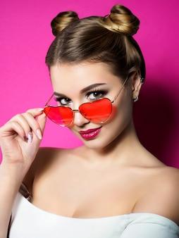 若い美しい遊び心のある女性は、彼女のハート型の赤い眼鏡を見ています。バレンタインデー、愛やテーマパーティーのコンセプト。スモーキーな目と赤い唇が構成されています。