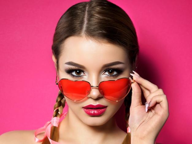 若い美しい遊び心のある女性は、彼女のハート型の赤い眼鏡を見ています。バレンタインデー、愛やテーマパーティーのコンセプト。スモーキーな目と赤い唇のメイク。