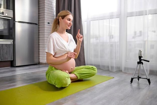 Молодая красивая приятная дама записывает видео онлайн-перевод на мобильный телефон, показывая упражнения йоги