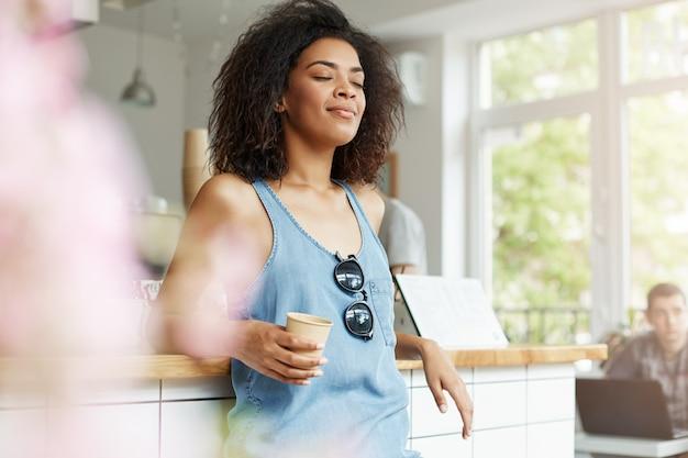 Ослаблять кофе молодой красивой довольной африканской женщины усмехаясь выпивая отдыхая в кафе. закрытые глаза.