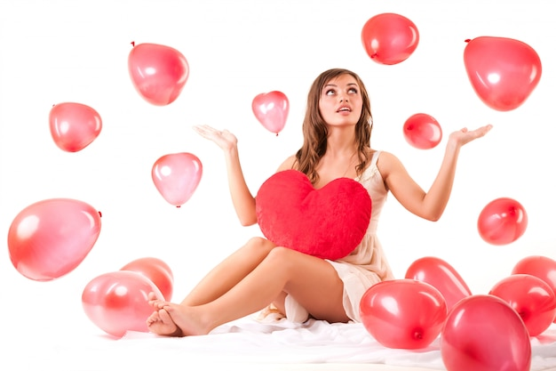 붉은 심장 모양의 풍선 비행에 앉아 베이지 색 드레스에 젊은 아름 다운 긍정적 인 갈색 머리 여자