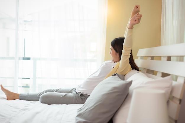 笑顔でベッドの上の腕を伸ばして若い美しい妊娠中のアジア女性