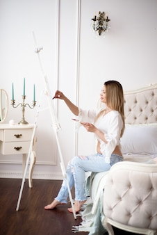 Young beautiful pregnant woman artist painting at home pink peonies