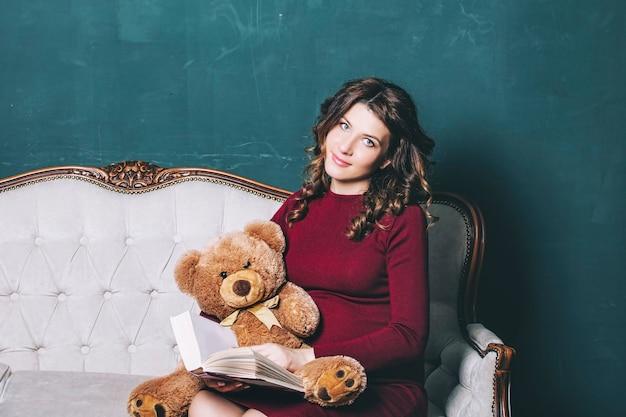 테디 베어를 손에 들고 집에 있는 젊은 아름다운 임산부