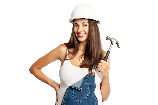 Young beautiful pregnant woman in a helmet with a hammer in her hand. isolated on a white background.