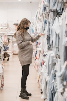 Young beautiful pregnant woman in hygienic mask choosing baby clothes for newborn.