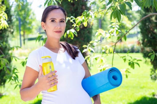 Молодая красивая беременная женщина в белой футболке занимается фитнесом в парке. держит коврик для йоги и спорта и бутылку чистой воды