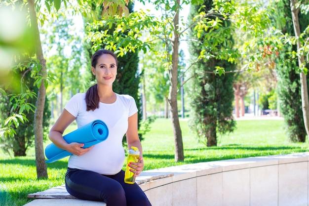 Молодая красивая беременная женщина в белой футболке занимается фитнесом в парке