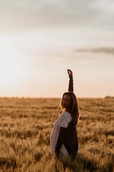 화창한 여름 날에 밀 오렌지 필드에 걸어 흰 드레스에 젊은 아름 다운 임신 한 여자. 팔을 하늘로 뻗어 자유를 느껴보세요. 기적의 기대. 격리에 일몰입니다. 태양 눈부심.
