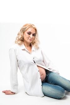 Молодая красивая беременная женщина, стоящая на белом