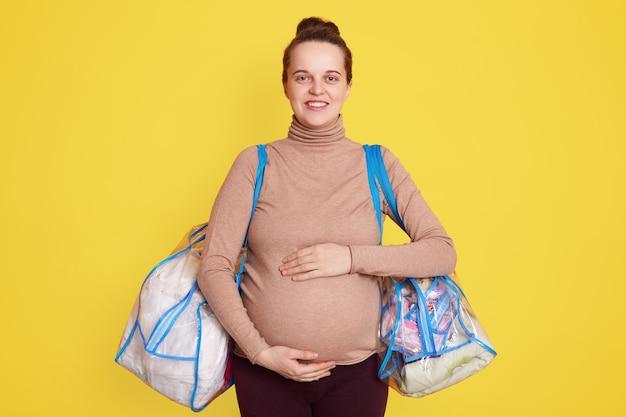 Молодая красивая беременная женщина, стоящая на желтой стене, держит сумки с вещами для лежания в больнице, держа руки на животе, готовая к родам в первый раз.