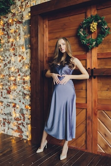 スタジオの近くでポーズをとってファッショナブルな赤いドレスを着たブロンドの髪と優しい化粧の若い美しい妊婦