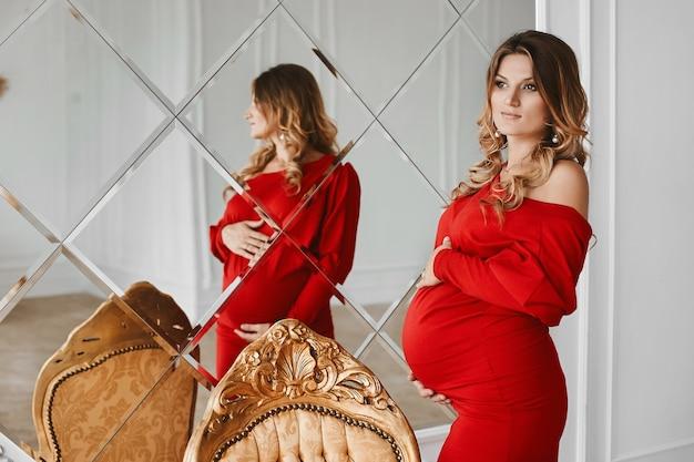 Молодая красивая беременная женщина со светлыми волосами и нежным макияжем в модном красном платье позирует возле большого зеркала в студии