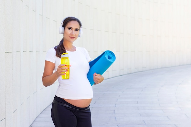 Young beautiful pregnant woman with fitnessmat