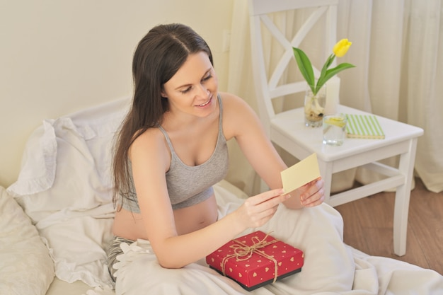 선물 상자를 들고 있는 젊고 아름다운 임산부, 침대에 앉아 인사말 카드를 읽는 여성