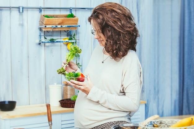 집에서 부엌에서 건강한 채식 식사와 함께 젊은 아름 다운 임신 한 여자