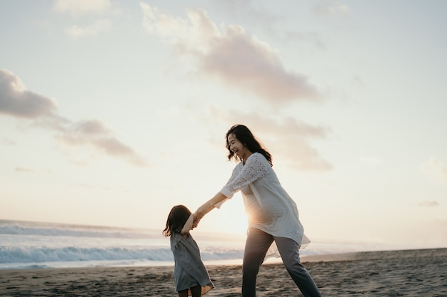 Young beautiful pregnant woman with her little cute daughter playing in the beach
