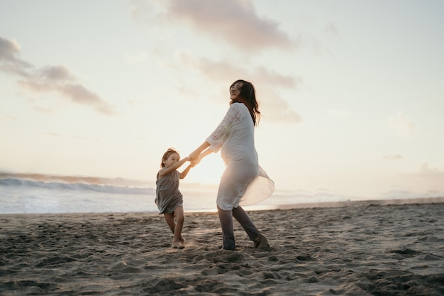 Молодая красивая беременная женщина с ее маленькой милой дочерью, играя на пляже