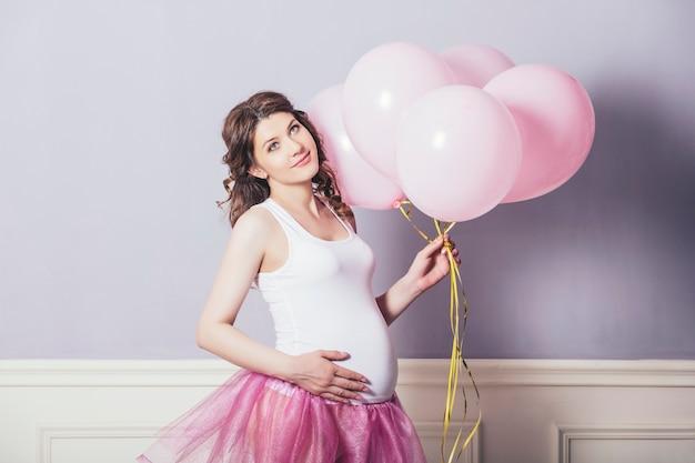 분홍색 풍선과 복고풍 배경에 분홍색 발레 치마를 입은 젊은 아름다운 임산부