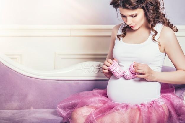 분홍색 니트 부츠와 복고풍 배경에 분홍색 발레 스커트를 입은 젊은 아름다운 임산부