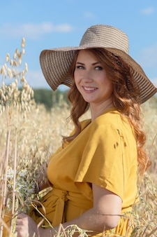 A young beautiful pregnant woman in a yellow dress and hat walks through a wheat orange field on a sunny summer day