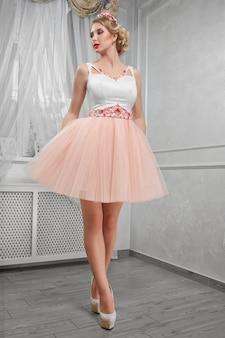 Молодая красивая, красивая женщина в светло-розовом коротком платье с красным