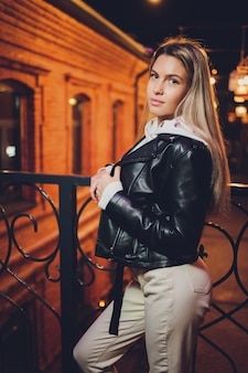 Молодая красивая красивая женщина улыбается и позирует на городской улице в ночное время на фоне боке вечерних огней.