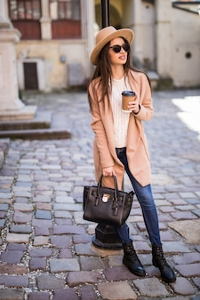 Young beautiful pretty woman walking along the street with handbag and cup of coffee.