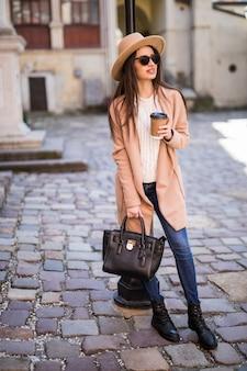 ハンドバッグと一杯のコーヒーが付いている通りに沿って歩く若い美しいきれいな女性。