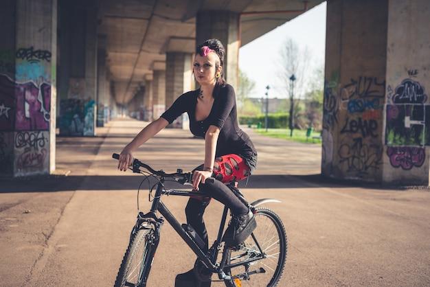 Young beautiful punk dark girl riding bike