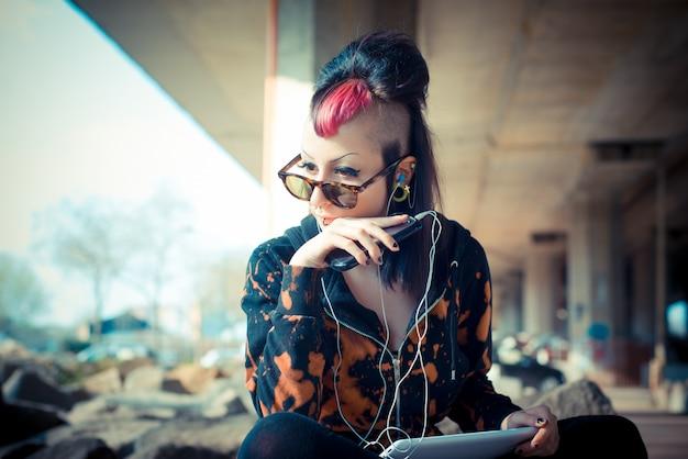 Young beautiful punk dark girl using tablet