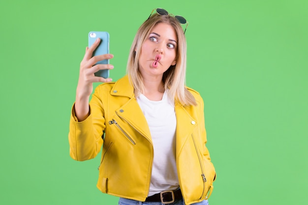 Young beautiful rebellious woman with blond hair against chroma key on green