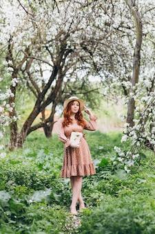 若い美しい赤い髪の少女は、春に咲くリンゴの果樹園を歩きます