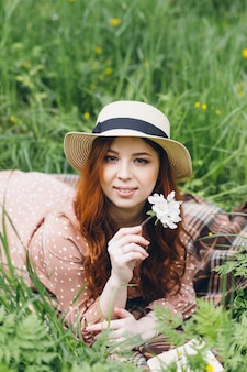 Young beautiful red-haired girl walks in a spring blooming apple orchard. tinting.