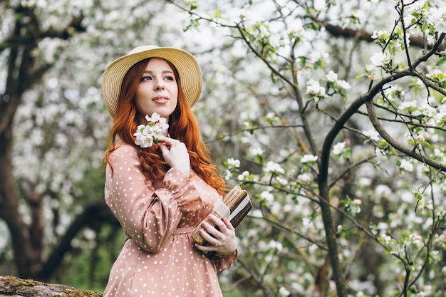 Young beautiful red-haired girl walks in a spring blooming apple orchard